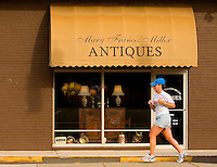 A woman runs down the street past an Antiques shop in the Myers Park neighborhood in Charlotte, NC. Myers Park is one of the premier neighborhoods in North America and known for its large canopy of trees.
