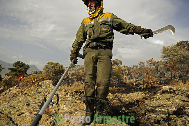 A member of the fire brigade walks around the area where a fire burns in the Cerro del Castillo hill near the town of Collado Mediano, northeast of Madrid, which forced the evacuation of some 2,000 people, the mayor of the town, Maria Rubio, told news radio Cadena Ser on July 21, 2009. Four firefighters were killed and two were seriosuly injured Tuesday as they battled another wildfire in a natural park in northeastern Spain, a spokeswoman for the local government said. on July 21, 2009. (C) Pedro ARMESTRE