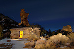 The jagged spire of the Broken Cross rock formation looms in the background of this nighttime view of the historic Swasey pioneer cabin, located near Eagle Canyon in the rugged San Rafael Swell area of Utah.