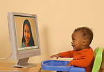 8 month old baby boy looking at and responding to human face on conputer monitor horizontal