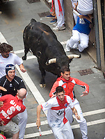 Participants run with Fuente Ymbro fighting bulls during the seventh San Fermin Festival´s running of the bulls, on July 13, 2013, in Pamplona, Basque Country. On each day of the eight San Fermin festival days six bulls are released at 8:00 a.m. (0600 GMT) to run from their corral through the narrow, cobbled streets of the old navarre town over an 850-meter (yard) course. Ahead of them are the runners, who try to stay close to the bulls without falling over or being gored. (Ander Gillenea / Bostok Photo)