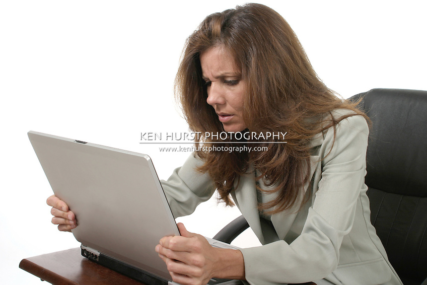 Attractive executive business woman working on a laptop computer frustrated with work.
