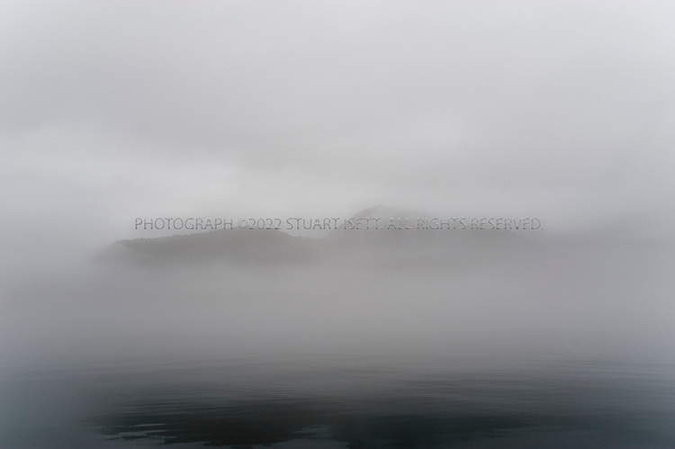 9/18/2008--Petersburg, Alaska, USA..The Sukoi Islands appear through fog  in Frederic Sound on the way to the Cascade Creek Cabin in Thomas Bay...Petersburg is on the north end of Mitkof Island, near the Tongass National Forest. A major fishing port, the town of 3500 is also a good jumping off point to see the Alaskan wilderness in south eastern Alaska. Petersburg can be reached on Alaskan Airlines via Seattle or nearby Juneau to the north...©2008 Stuart Isett. All rights reserved.