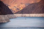 """A boat in Lake Mead below the rim of Boulder Canyon and upstream from Hoover Dam, Nev.. The white """"bathtub ring"""" shows the draw-down of the pool elevation after several years of drought."""