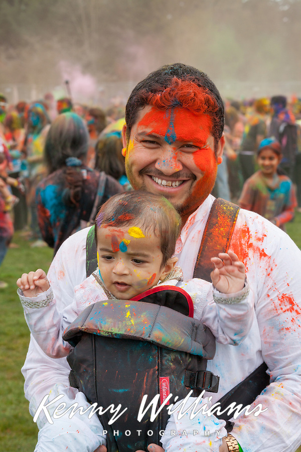 Muslim man carrying his baby daughter, Holi Festival of Colors, Bellevue, WA, USA.