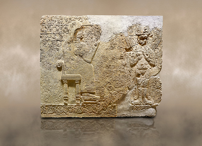 """Photo of Hittite relief sculpted orthostat stone panel  of Long Wall Limestone, Karkamıs, (Kargamıs), Carchemish (Karkemish), 900-700 BC. Anatolian Civilisations Museum.<br /> <br />  The hieroglyphics reads; """"I am Win-a-tis, beloved wife of my Lord Suhi, wherever and whenever my husband honours his name, he will honour my name as well with favours"""". Underneath, there are two goddess figures, one is naked with a horned head, holding her breasts with her hands. Her genitalia is indicated by a triangle. <br /> <br /> On a brown art background."""