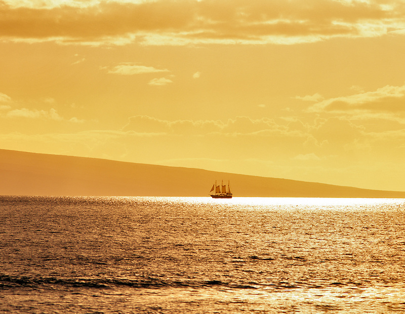 Backlit old time sailing ship at sunset. Island of Lanai in back. Shot from Maui, Hawaii