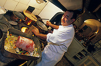 France/84 Vaucluse/Avignon: Table d'Hote de la Mirande dans la cuisine médiévale d'un ancien palais de Cardinal Jean Claude Altmayer prépare le roti de veau à la cardamone et échalote confite au fourneau à bois