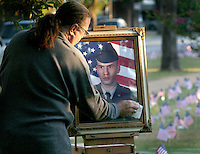Max Branham polishes the picture of his late stepson, Sergeant Jeremy Smith, before a commemoration ceremony in the Heights for the 2,000th soldier killed in Iraq in 2005.