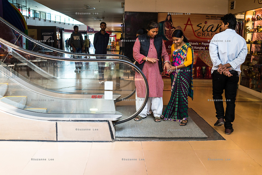 Santwana Manju of Guria holds Brinda's hand as she takes an escalator for the first time while out for a day of shopping fun in Varanasi, Uttar Pradesh, India on 24 November 2013. Manju takes the girls under the witness protection program out shopping once in a few months to ease their minds and help them prepare for the court appearances.