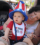 A toddler with his mother watching the Saugerties July 4th Parade on Main Street in Saugerties, NY on Monday, July 4, 2011. Photo by Jim Peppler. Copyright © Jim Peppler 2011.