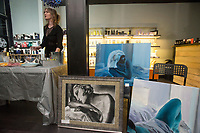 NWA Democrat-Gazette/BEN GOFF @NWABENGOFF<br /> Kyndall Wood serves refreshments as art by Katie Russell sits on display Thursday, Nov. 9, 2017, at Urban Bleu hair salon during the first Art on the Bricks event in downtown Rogers. More than 20 downtown Rogers businesses participated in the walk, hosting pop-up galleries, artist receptions and live music in what is planned as a regular event on the second Thursday of each month from 4:30p.m. to 6:30p.m.