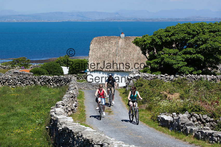 Ireland, County Galway, Aran Islands, Inishmore: White-washed thatched cottage with cyclists between dry stone walls and Galway Bay behind | Irland, County Galway, Aran Islands, Inishmore: Fahrradtour ueber die Insel, im Hintergrund geweisstes Reetdachhaus und Galway Bay