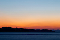 Sunset over the sea. View over the islands Daksa and others. House lights. Uvala Sumartin bay between Babin Kuk and Lapad peninsulas. Dubrovnik, new city. Dalmatian Coast, Croatia, Europe.