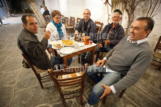 Friends gather for a dinner of lamb chops, potatoes, wine and bread in the village square, Chora, Folegandros, Cyclades, Greece