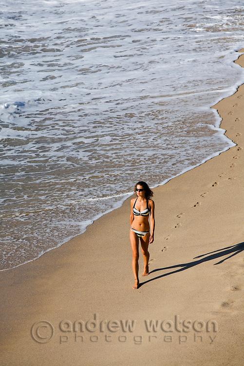 A woman walks along the sands of Tamarama Beach.  Sydney, New South Wales, AUSTRALIA.