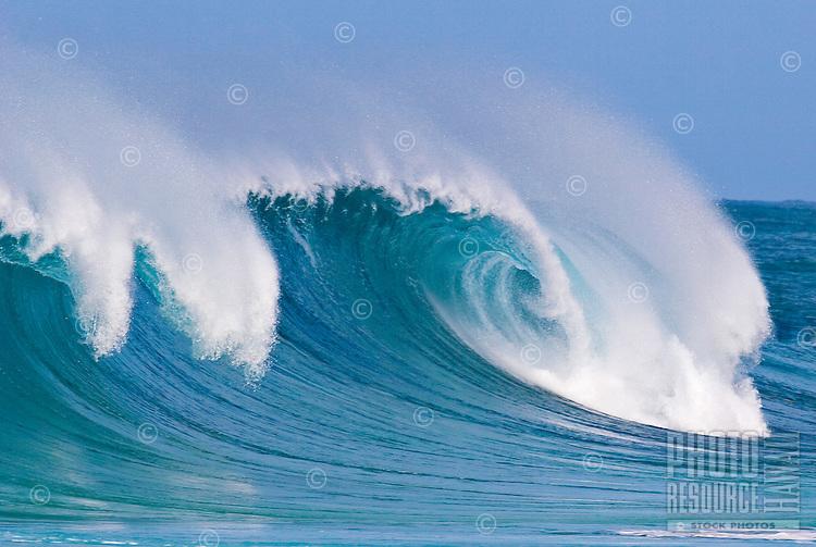 Wave breaking near rock piles surf break on the north shore of Oahu.