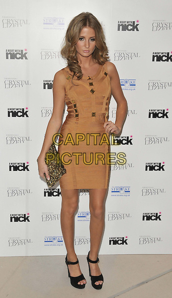 "Millie Mackintosh.The ""A Night With Nick"" charity event in aid of The Stroke Association, Swarovski CRYSTALLIZED, Gt. Marlborough St., London, England..December 6th, 2011.full length beige brown gold dress black sandals ankle straps clutch bag hand on hip .CAP/CAN.©Can Nguyen/Capital Pictures."