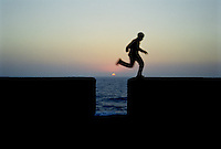 A boy jumping over the cannon opening of the rampart wall in Essouira Morocco at Sunset