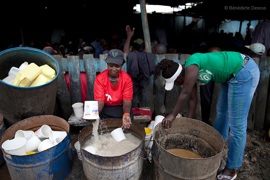 Two Kenyan women washes plastic bucket at the Madiaba Busaa Club in a Nairobi slum on March 27, 2013. Busaa, a traditional fermented beer, is made by crudely fermenting maize, millet, sorghum or molasses. At Kshs 35 per liter it is much cheaper than a Kshs120 half-liter bottle of commercial beer. The local brew was legalised in 2010 and since then busaa clubs have become increasingly popular. Drinking is on the rise in Kenya, especially among young people. Photo by Benedicte Desrus