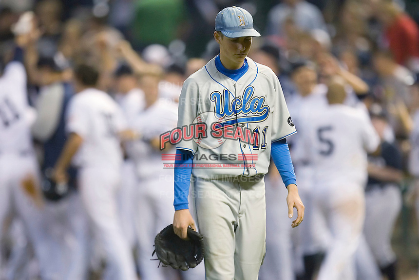 A dejected Trevor Bauer #11 of the UCLA Bruins walks off the field as the Rice Owls celebrate their 5-4 win in the bottom of the 10th inning in the 2009 Houston College Classic at Minute Maid Park February 27, 2009 in Houston, TX.  (Photo by Brian Westerholt / Four Seam Images)