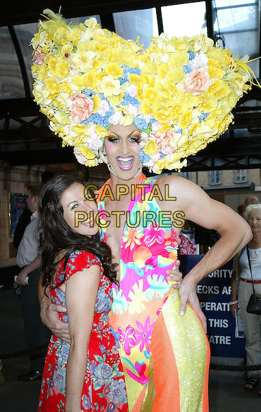 "HAYLEY TAMADDON & CAST MEMBER.""Priscilla: Queen Of The Desert The Musical"" - Cast Change, London, England, UK..June 22nd, 2010.arrivals half length blue dress red floral print tea brown drag queen hat character costume yellow flowers .CAP/WIZ.© Wizard/Capital Pictures."