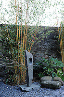 In a private walled garden, a tranquil space with a line of bamboo softening the brickwork around it, a small Barbara Hepworth sculpture is nestled within it.