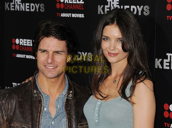 "TOM CRUISE & KATIE HOLMES.arriving at the world premiere of ""The Kennedys"" held at the Samuel Goldwyn Theatre at the Academy of Motion Picture Arts and Sciences in Beverly Hills, California, USA, March 28th, 2011. .portrait headshot husband wife married couple brown leather jacket green blue buttons vest sleeveless shirt S initial necklace gold letter tall short .CAP/ROT/TM.© TM/Roth/Capital Pictures"