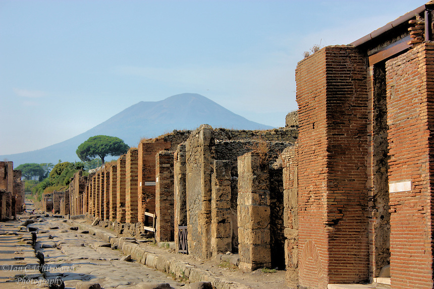 With Mount Vesuvius in the background, a view down a road at the ruins at Pompeii