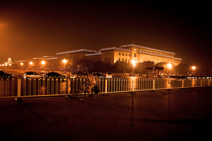 Two beijingers are passing near the People's Palace (CPC headquarters) and the Chang'an avenue, on the west side of Tiananmen square, the evening before the celebration of the CPC 90 Years anniversary 2011.