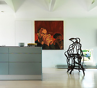 A large oil painting by Peter Hocking and a chair by Carl Hirsch made out of laurel branches with a tractor seat