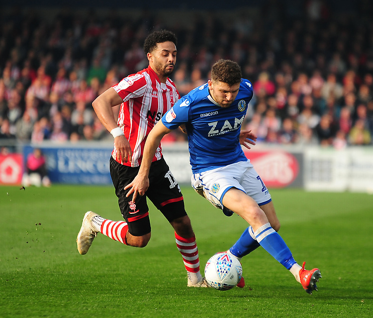 Macclesfield Town's James Pearson shields the ball from Lincoln City's Bruno Andrade<br /> <br /> Photographer Andrew Vaughan/CameraSport<br /> <br /> The EFL Sky Bet League Two - Lincoln City v Macclesfield Town - Saturday 30th March 2019 - Sincil Bank - Lincoln<br /> <br /> World Copyright © 2019 CameraSport. All rights reserved. 43 Linden Ave. Countesthorpe. Leicester. England. LE8 5PG - Tel: +44 (0) 116 277 4147 - admin@camerasport.com - www.camerasport.com