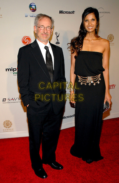 STEVEN SPIELBERG & PADMA LAKSHMI.34th International Emmy Awards Gala at the New York Hilton, New York, NY, USA..November 20th, 2006.full length black suit dress strapless silver belt bracelet clutch purse.CAP/ADM/PH.©Paul Hawthorne/AdMedia/Capital Pictures *** Local Caption ***