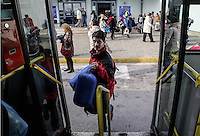 Pictured: A male migrant about to board a bus Monday 08 Fabruary 2016<br /> Re: Migrants wait in the Piraeus passenger station to be transported to the migrants' camp in Elliniko, Athens, Greece