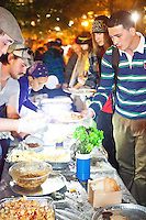 "People line up for free dinner, prepared for and by protesters, as the protest ""Occupy Wall Street"" continues into its third week in Zuccotti Park in New York City on October 6, 2011."