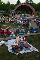 A couple reclines on a blanket on the grass to listen to an outdoor concert at the ampitheater in Alum Creek Park in Westerville as part of a summer concert series.