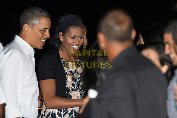 United States President Barack Obama and first lady Michelle Obama greet well wishers before boarding Air Force One for their return flight to Washington at Joint Base Pearl Harbor-Hickam on Saturday January 5, 2013 in Honolulu, Hawaii. .half length white shirt smiling side profile dress print married husband wife cardigan .CAP/ADM/CNP/KN.©Kent Nishimura/CNP/AdMedia/Capital Pictures.
