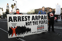 Mesa, Arizona. February 23, 2012 - As Republican candidates debated in the Mesa Arts Center, protesters including undocumented students, tea partiers, occupy movement members and Syrian president opponents, shouted slogans and held up signs and placards outside. In this photograph, activits from the Arizona immigrant rights Puente Movement hold a banner against immigration enforcement tactics of Maricopa County Sheriff Joe Arpaio. Arpaio is an aggressive enforcer of immigration laws and has arrested thousands of immigrants. Photo by Eduardo Barraza © 2012