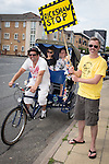 © Joel Goodman - 07973 332324 . 27 July 2013 . Hulme Community Garden Centre , Old Birley Street , Hulme , Manchester M15 , UK . L-R Steve Owen of Smiles per Hour Rickshaw and Tuck Tuck of Blackpool in the saddle , Susannah Shrubsole from Sale , Nathan Green from York  and Robert Johnson from Chorlton (all correct) holds up the temporary Richshaw Stop sign , opposite the garden centre . Hulme is Where the Art Is festival . Photo credit : Joel Goodman