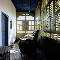 Light filters through a green painted grille into a bedroom where the ceiling and door are painted blue.