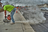 Worker cuts fresh sidewalk laid as part of a road-widening improvement project on South State Street in Westerville OH.