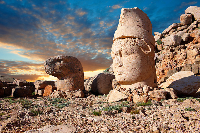 Pictures of the statues of around the tomb of Commagene King Antochus 1 on the top of Mount Nemrut, Turkey. Stock photos & Photo art prints. In 62 BC, King Antiochus I Theos of Commagene built on the mountain top a tomb-sanctuary flanked by huge statues (8–9 m/26–30 ft high) of himself, two lions, two eagles and various Greek, Armenian, and Iranian gods. The photos show the broken statues on the  2,134 m (7,001 ft)  mountain. 7
