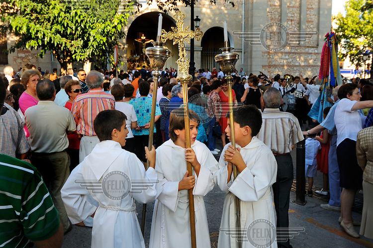 A group of altar boys wait for the beginning of a Catholic religious procession through the town of Campo de Criptana.