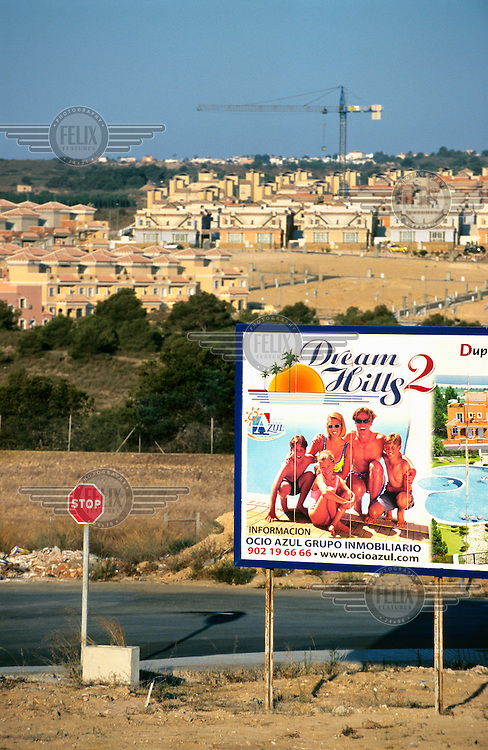 A billboard advertising a new property development stands next to a stop sign near a housing construction site. In recent years there has been an explosion of controversial tourist-focused developments in Spain's arid southeastern region causing environmental degradation and placing enormous pressure on the limited amenities in the area. Much of the new housing is sold to foreign buyers who predominantly use or rent the properties as holiday homes.