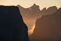 Midnight light shines between vertical peaks of Moskenesøy, Lofoten Islands, Norway