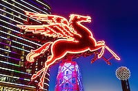 """Pegasus - Dallas, Texas"" - Pegasus, the 'Flying Red Horse', was built atop the Renaissance Revival Magnolia Building (now known at the Magnolia Hotel), by Texlite for the Magnolia Oil Company in 1934. Standing majestically at 450 feet above ground level, the Dallas icon was visible 75 miles away on a clear night. Pilots reported catching sight of it 60 miles south of Hillsboro, and some claimed to see it from as far away as Waco. By 1974, the landmark had experienced structural and weathering issues, and in 1999 a crane and helicopter aided in the removal of the two original forty foot horses. For the city's Y2K Millennium Celebration, the original horses were used as templates to create a brand new winged horses, with the new horses lit high above the Magnolia. The original 1934 winged horses were renovated by Omni Dallas developer Matthews Southwest and set atop a 22 foot oil derrick. Illuminated and mounted, the original Pegasus (pictured) can be viewed in all its glory outside of the magnificent Magnolia Hotel in downtown Dallas."