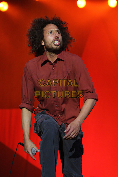 RAGE AGAINST THE MACHINE - Zack De La Rocha.Perform as part of 'Rage Factor' at Finsbury Park, London, England, UK, June 6th 2010..music gig concert live on stage .half length microphone  red shirt beard facial hair mouth open funny .CAP/MAR.© Martin Harris/Capital Pictures.