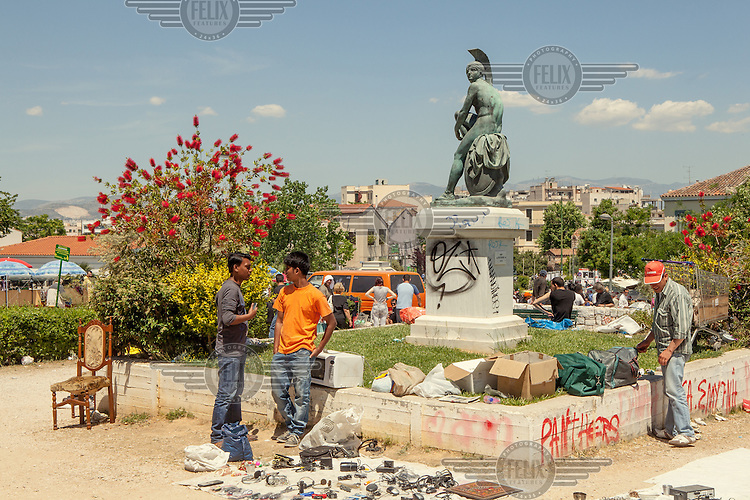 ATHENS, GREECE: migrants selling things close to a statue of Pericles at the flea market