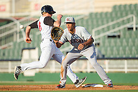Ronald Guzman (22) of the Hickory Crawdads waits for a pick-off throw as Carl Thomore (13) of the Kannapolis Intimidators heads back to first base at CMC-Northeast Stadium on May 18, 2014 in Kannapolis, North Carolina.  The Intimidators defeated the Crawdads 6-5 in 10 innings.  (Brian Westerholt/Four Seam Images)