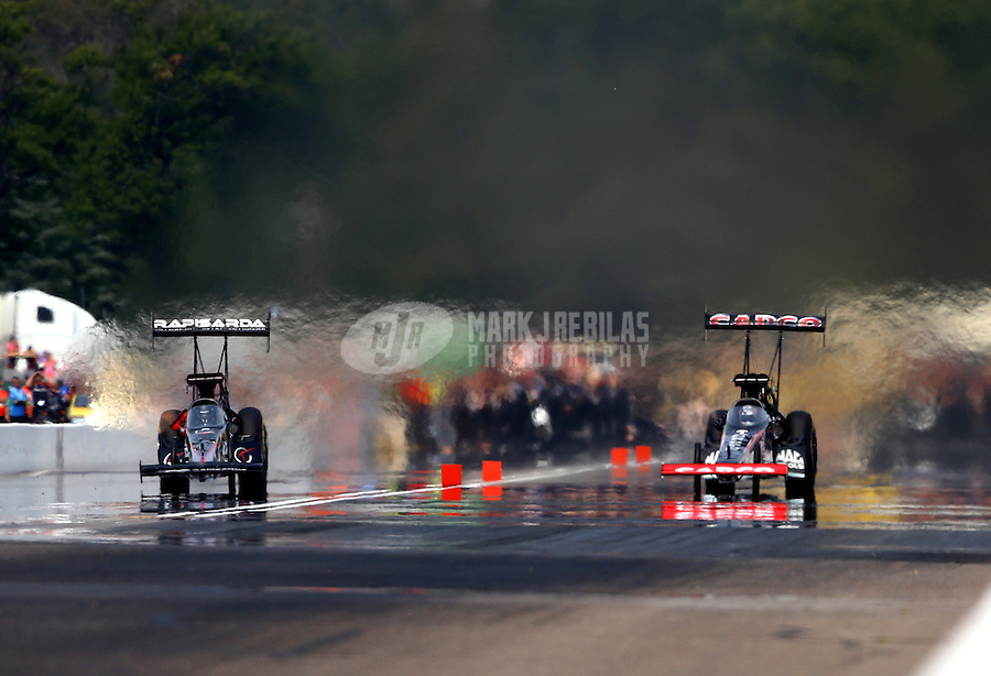 Aug. 18, 2013; Brainerd, MN, USA: NHRA top fuel dragster driver Steve Torrence (right) races alongside Tommy Johnson Jr during the Lucas Oil Nationals at Brainerd International Raceway. Mandatory Credit: Mark J. Rebilas-